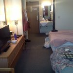 open closet area left of door, tv, coffee pot on dresser,