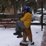 15-year-old grandson in Woodie the Bear's arms next to condos - ski parking lot in the backgroun