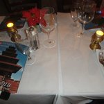 Clean White Tablecloths, Romantic Table Candles, Restaurant Menu, & Miniature Holiday Red Poinse