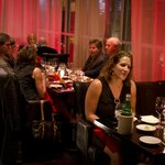 Patrons mingling under the red ambient glow of the dining room