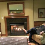 My husband enjoying the wonderful fireplace in the lobby!  It also opens into the breakfast room