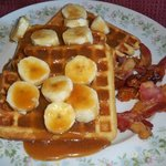 Buttermilk waffles topped with bananas in caramel and bacon
