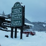 Crystal Mt Lodging Sign with Silver Ski Chalet in Background