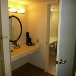 room with coffee maker, bathroom is next door