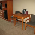 Television, microwave, and mini-fridge along with a table, two chairs, and a c