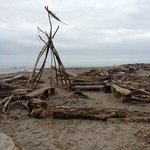 someone made a teepee on the beach with benches and all