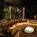 seating area with a fire pit, gas grill, and swim up barstools