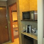 Microwave, coffee maker, and fridge in room.