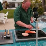 my husband cooking lunch for us on the grill by the pool