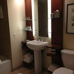  Awkward bathroom set up for two.  Small glass shelves from which your belongings slide off.