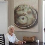                    My Mom at our table with one of those beautiful paintings behind her