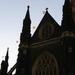 Four hot air balloons hover above St Patrick's Cathedral, Melbourne