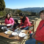 Having tasty breakfast in front of cottage lawns ,behind is Annapurna range  Nepal