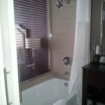 Bathroom features lovely, relaxed back bath tub, soft lighting, and Aveda amenities