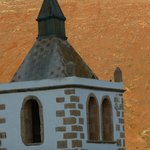  Church turret against hillside turning red in the evening sun