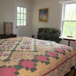  View of quilt on bed and loveseat in room.  Door leads to outdoor balcony to relax outside.