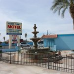 Front of motel with sign and fountain