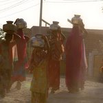  Women carrying water through Chandelao