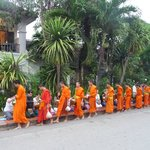 Monks passing the front of Villa Santi Hotel