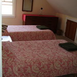 A third bedroom has pink bedspreads.
