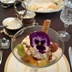 Grapes, orange pegs, yogurt and granola topped with an edible flower