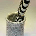 Classic Raku ware pot with a fountain pen in it