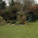 The beautiful little garden with a summer house and ducks in a pond