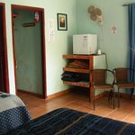 room showing closet, frige, shelf, fan, chair(2) and there is a small table