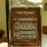 Chocolate on the bed with a picture of the hotel