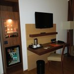 Hotel room desk, television, mini-bar.