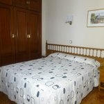 Double room with ensuite bathroom has closet, desk & chair.
