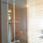 The glass-enclosed shower with louvre blind