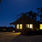 Redgum Cottage glowing by night.