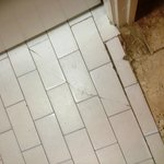 Tiling and attempted repairs at kitchen doorway.