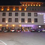 front of the hotel seen in the night and half of its parking