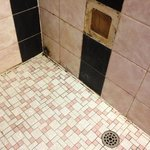  Motel single room - shower with missing tile and in-ground mould