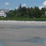 The beach and dunes in front of the buildings of Acadia Oceanside Meadows Inn