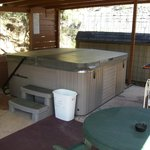8 person hot tub covered area with gas grill and patio area