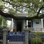 The welcoming porch and classic New Orleans oak at Sully Mansion.