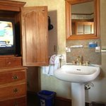 tv is in the cabinet, sink is outside the bathroom