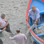  Fishermen tending their nets on the beach below the parador.