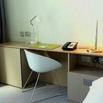 Desk area with four UK power outlets. More outlets available by television and floating shelf an