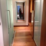  hallway with mirror near entryway, flanked by bathroom on the left, closet on the right