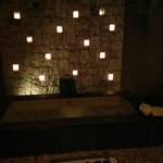 Bathtub at night, candles lit in the wall and rose petals, set up by room service with complimen