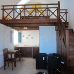 The room from the balcony door looking in. The bed is upstairs. Kitchenette and bathroom in the