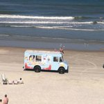 Ice cream truck driving down the beach by hotel