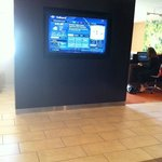 Lobby TV screen with weather info