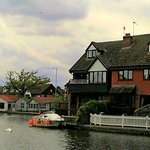 Cottages are behind the white paling fence, Wroxham Bridge to the left