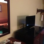 flat screen tv, desk/table, and couch area in our room