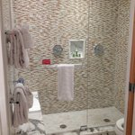 Double shower with marble floors and bench in the shower all enclosed in glass